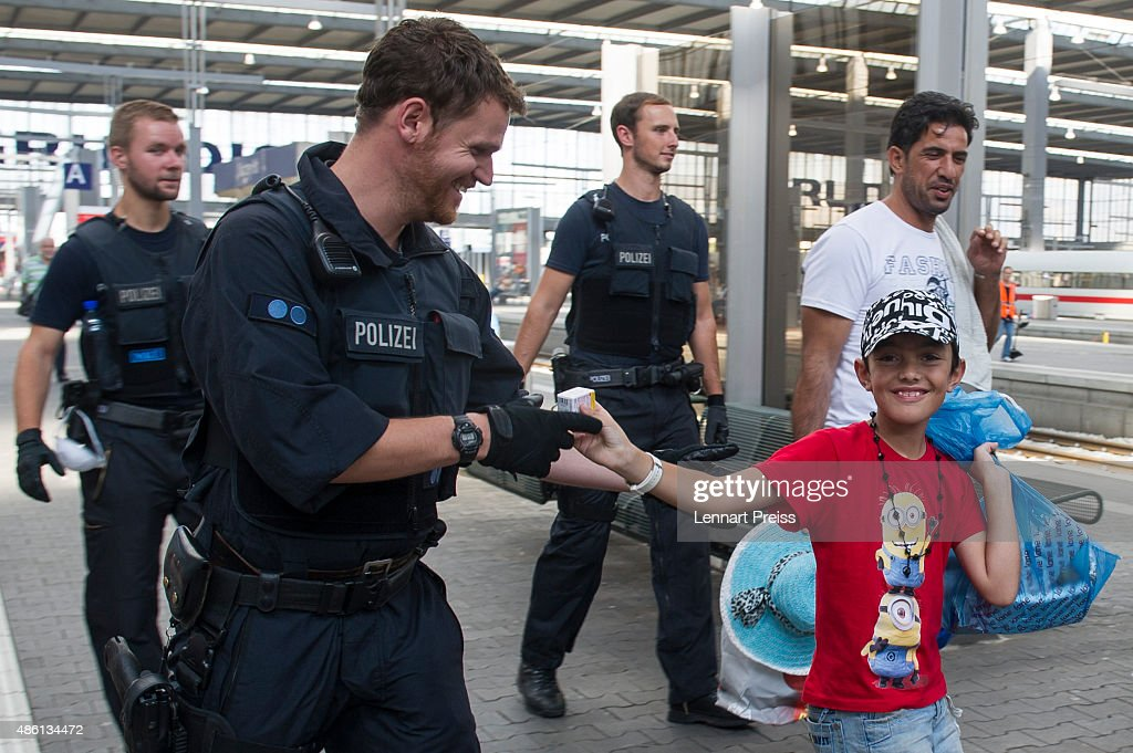 A migrant boy (R) hands over a pack of glucose to a policeman as police detain migrants who arrived at Munich Hauptbahnhof main railway station without passports or valid visas on September 1, 2015 in Munich, Germany. Over a thousand migrants arrived in southern Germany by train in the last 24 hours, many of them who boarded trains in Budapest. According to police hundreds of migrants are arriving in southern Germany daily, either via people smugglers from Hungary along the A3 highway or via trains coming from Italy. Germany is expecting to receive 800,000 asylum-seeking migrants this year and is struggling to cope with the record number.