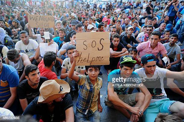 Migrant boy holds a sign reading 'SOS help me' as he sits with other migrants in front of the Keleti railway station in Budapest on September 2 2015...