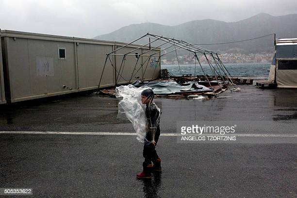 A migrant boy tries to put on a rain coat at the registration center on the Greek island of Samos on January 17 2016 / AFP / ANGELOS TZORTZINIS