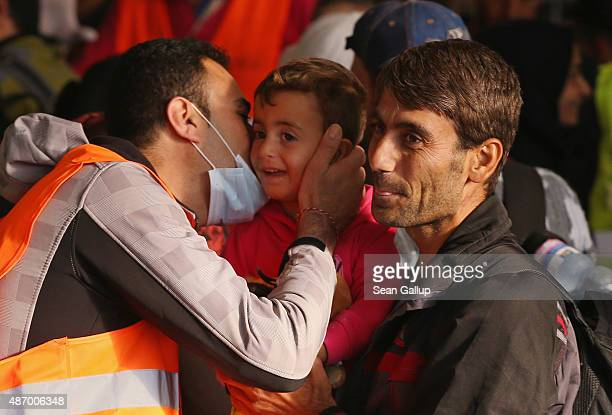 A migrant boy who had arrived on a train from Hungary gets a kiss from a volunteer worker at Munich Hauptbahnhof main railway station on September 5...