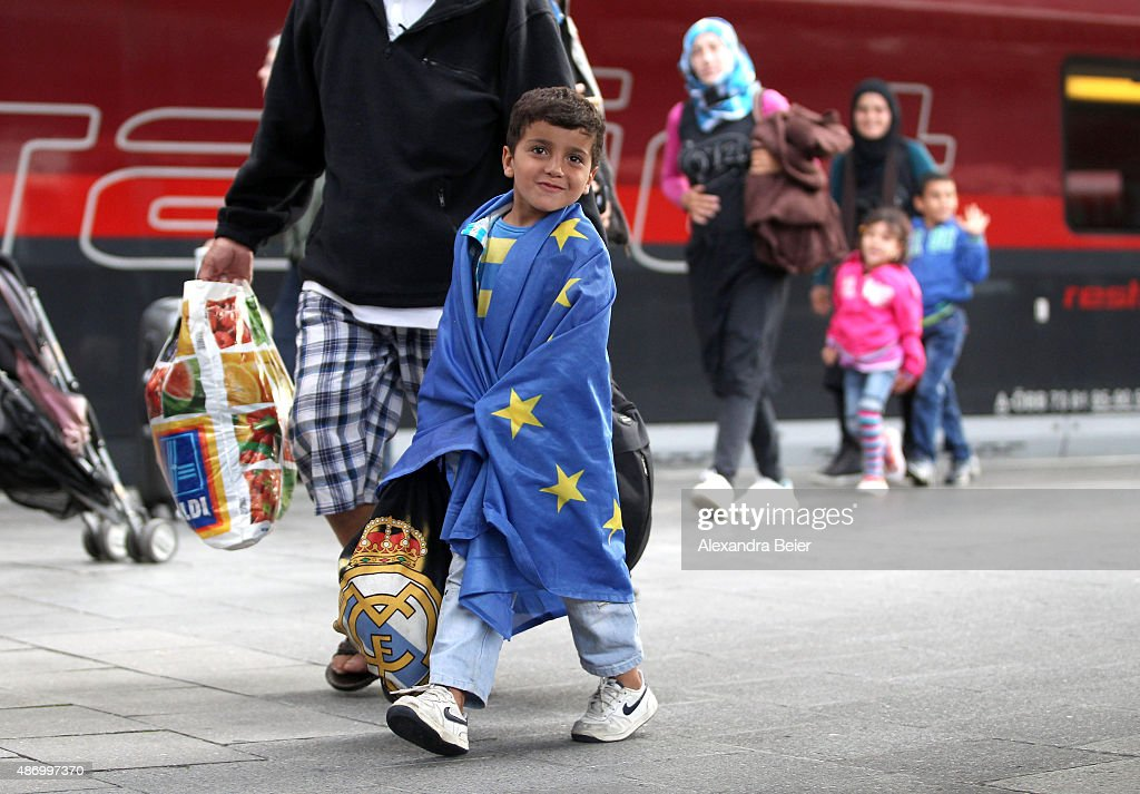 A migrant boy wrapped in an EU flag arrives from Austria at Munich Hauptbahnhof main railway station on September 5, 2015 in Munich, Germany. Thousands of migrants are traveling to Germany following an arduous ordeal in Hungary that resulted in thousands walking on foot and then being bussed by Hungarian authorities from Budapest to the Austrian-Hungarian border.