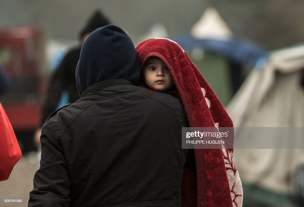 A migrant carries a child in the migrants camp of Grande-Synthe, near Dunkirk, on January 20, 2016, where almost some 2,500 migrants and refugees live, mostly Iraqi Kurds and Syryans. Authorities in the northern French port of Calais were struggling to move hundreds of migrants into refitted shipping containers ahead of plans to bulldoze part of the notorious 'Jungle' camp. There wre also attempts to relocate 2,500 migrants camped some 40 kilometres (25 miles) up the road from Calais in Grande-Synthe. HUGUEN