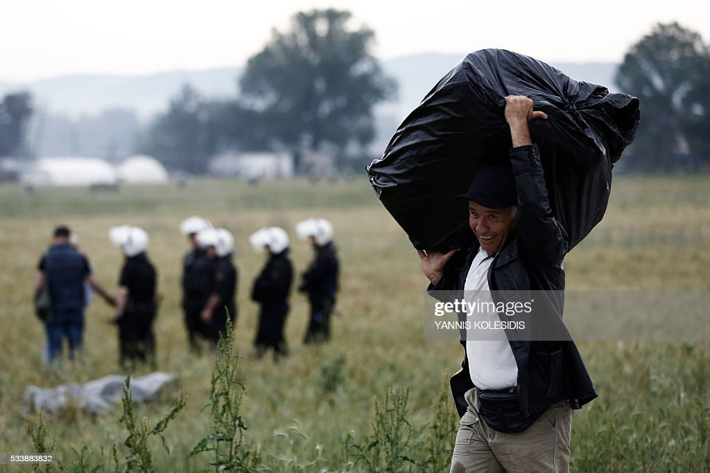 A migrant carries his belongings during an evacuation operation by police forces of a makeshift migrant camp at the border at the Greek-Macedonian border near the village of Idomeni, on May 24, 2016. In an operation which began shortly after sunrise on May 24, hundreds of Greek police began evacuating the sprawling camp which is currently home to 8,400 refugees and migrants, among them many families with children, an AFP correspondent said. At its height, there were more than 12,000 people crammed into the site, many of them fleeing war, persecution and poverty in the Middle East and Asia, with the camp exploding in size since Balkan states began closing their borders in mid February in a bid to stem the human tide seeking passage to northern Europe. / AFP / POOL / YANNIS
