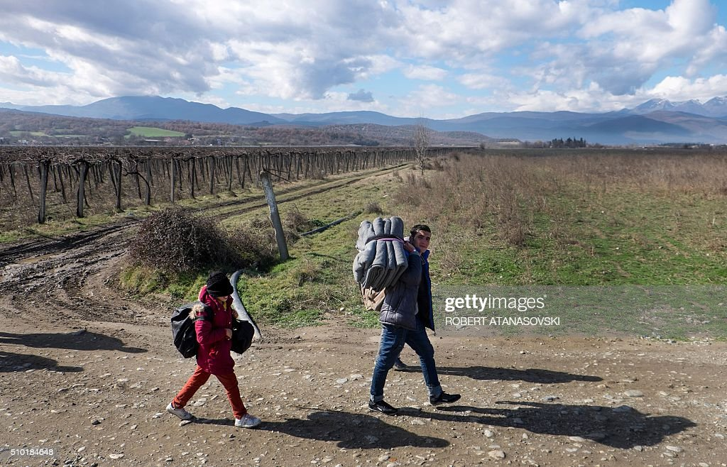 A migrant carrying blankets and a child, cross the Greek-Macedonian border near the town of Gevgelija, on February 14, 2016. Dutch Foreign minister Bert Koenders on February 14, 2016 spent an hour in a Vinojug recipient center near Gevgelija talking with migrants, children, UNICEF and Red Cross representatives, police and others members who are taking care of migrants heading to the EU from devastated homes in Syria, Afghanistan and Iraq. / AFP / Robert ATANASOVSKI