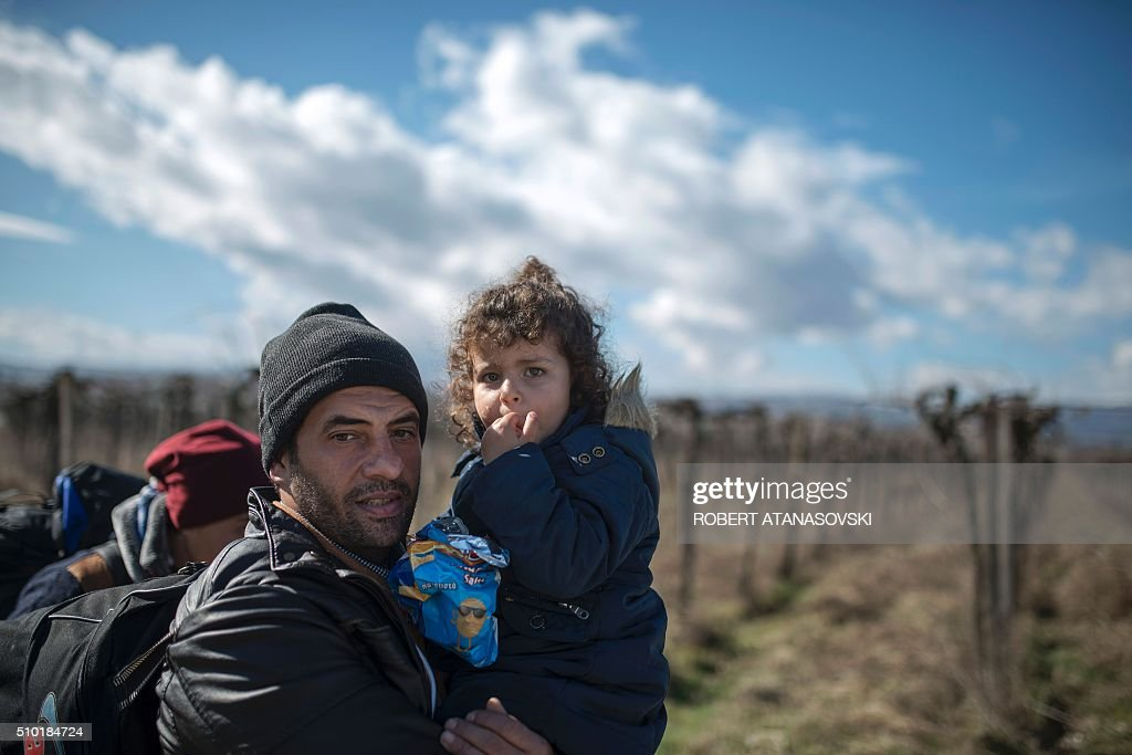A migrant carrying her child crosses the Greek-Macedonian border near the town of Gevgelija, on February 14, 2016. Dutch Foreign minister Bert Koenders on February 14, 2016 spent an hour in a Vinojug recipient center near Gevgelija talking with migrants, children, UNICEF and Red Cross representatives, police and others members who are taking care of migrants heading to the EU from devastated homes in Syria, Afghanistan and Iraq. / AFP / Robert ATANASOVSKI