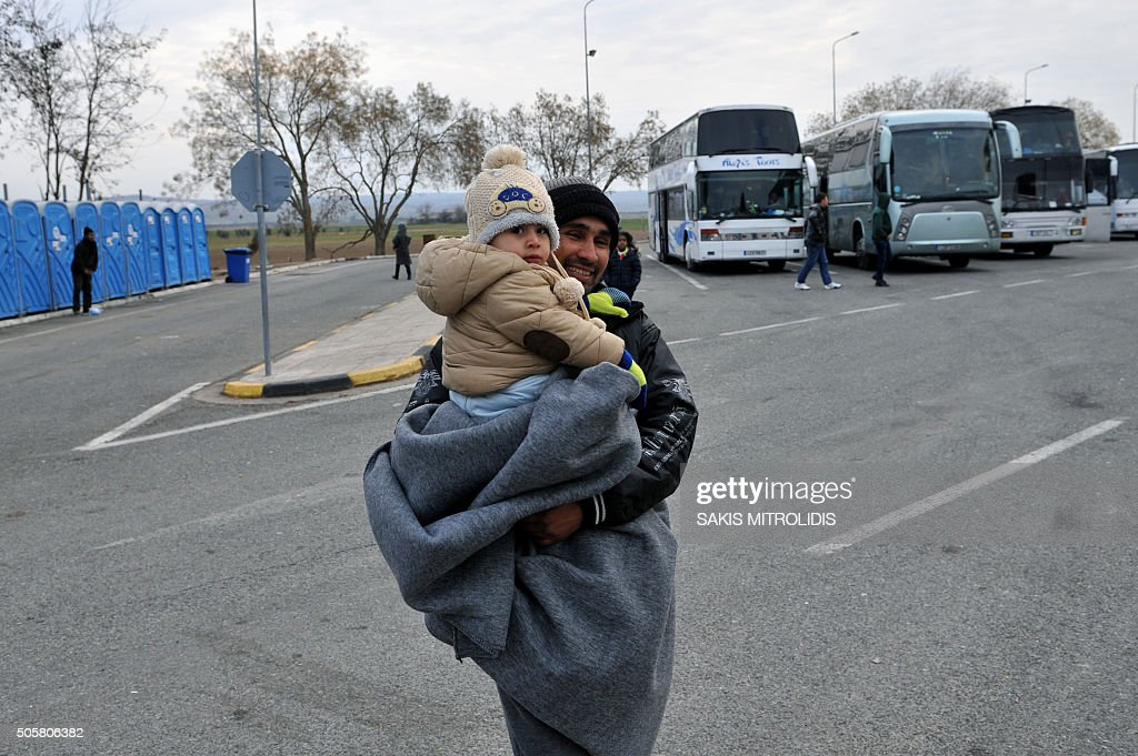 A migrant carrying his child stand next to buses as he waits to cross the GreekMacedonian border near Idomeni on January 20 2016 As refugees...