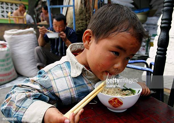 A migrant child eats his lunch near his father at a market on May 30 2005 in Beijing China According to official reports over 140 million migrant...
