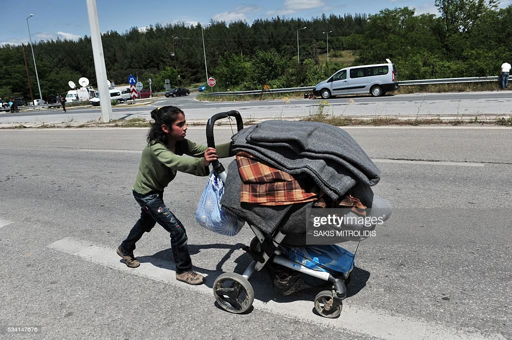 A migrant child pushes a pushchair filled with blankets, as he leaves on foot with others migrants the Idomeni camp along the Greek-Macedonian border because they do not want to be bussed to another camp on May 25, 2016. In an operation which began shortly after sunrise on May 24, hundreds of Greek police began evacuating the sprawling camp which is currently home to 8,400 refugees and migrants, among them many families with children, an AFP correspondent said. At its height, there were more than 12,000 people crammed into the site, many of them fleeing war, persecution and poverty in the Middle East and Asia, with the camp exploding in size since Balkan states began closing their borders in mid February in a bid to stem the human tide seeking passage to northern Europe. / AFP / SAKIS