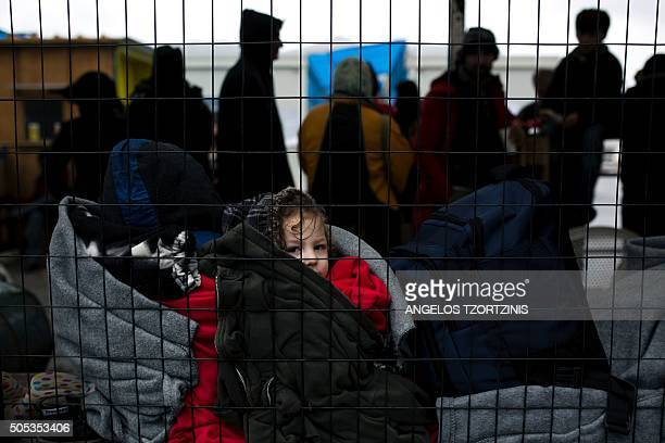 A migrant child sits onto a bench inside a registration center on the Greek island of Samos on January 17 2016 / AFP / ANGELOS TZORTZINIS