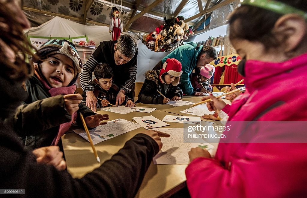 Migrant children attend a lesson in a makeshift school on February 10, 2016, in the so-called 'Jungle' migrant camp in Calais. Inaugurated early February, the makeshift structure, which can only welcome daily a twenty children of parents coming from Iraq, Syria or Afghanistan, was installed next to the adult classroom opened in July. / AFP / PHILIPPE