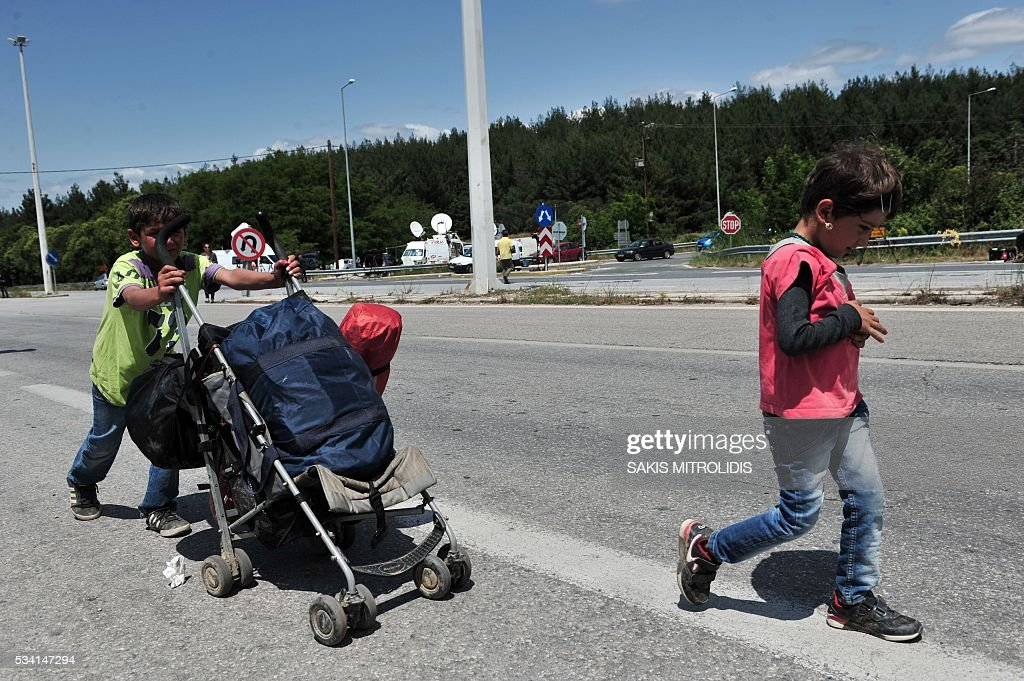 Migrant children leave on foot with others migrants the Idomeni camp along the Greek-Macedonian border because they do not want to be bussed to another camp on May 25, 2016. In an operation which began shortly after sunrise on May 24, hundreds of Greek police began evacuating the sprawling camp which is currently home to 8,400 refugees and migrants, among them many families with children, an AFP correspondent said. At its height, there were more than 12,000 people crammed into the site, many of them fleeing war, persecution and poverty in the Middle East and Asia, with the camp exploding in size since Balkan states began closing their borders in mid February in a bid to stem the human tide seeking passage to northern Europe. / AFP / SAKIS