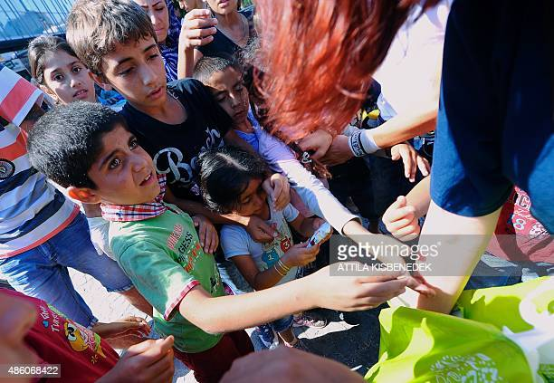 Migrant children receive snacks wait in front of the eastern railway station in Budapest on August 31 2015 The EU is grappling with an unprecedented...