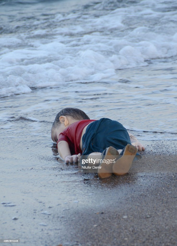 A migrant child's dead body (Aylan Shenu) lies on the shores in Bodrum, southern Turkey, on September 2, 2015 after a boat carrying refugees sank while reaching the Greek island of Kos. Thousands of refugees and migrants arrived in Athens on September 2, as Greek ministers held talks on the crisis, with Europe struggling to cope with the huge influx fleeing war and repression in the Middle East and Africa. AFP PHOTO / Nilufer Demir / DOGAN