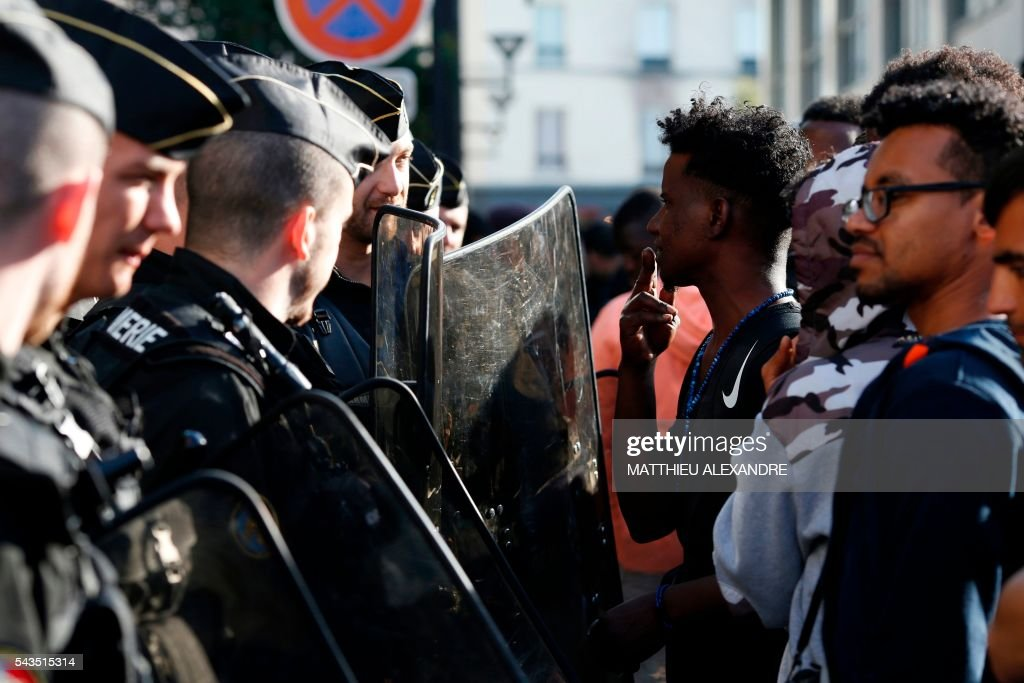 A migrant communicates with a French gendarme during the evacuation of his camp near the Pajol hall on June 29, 2016 in Paris. The police started early on June 29, 2016, the evacuation of several hundreds of migrants, from a camp at the former SNCF Hall 'Pajol'. / AFP / MATTHIEU