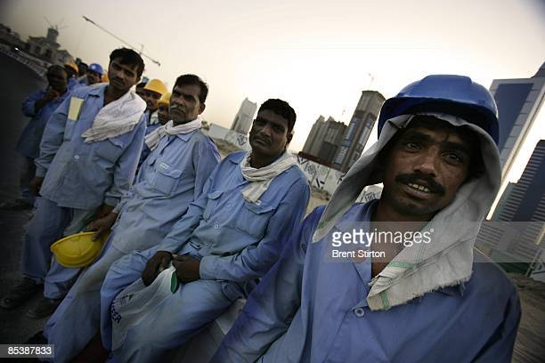 Migrant construction labourers working in Dubai line up to board a bus which will take them back to their labour camp for the night on May 1 2006 in...