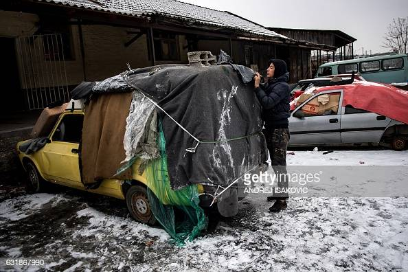 TOPSHOT A migrant covers an abandonned car he uses as a makeshift shelter near Belgrade's main railway station on January 17 with temperatures bellow...