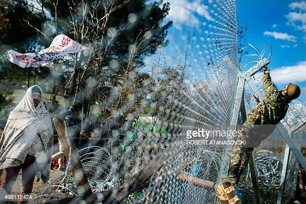A migrant demonstrate looks on from behind a fence as he wait to cross the GreekMacedonian border near Gevgelija on November 29 2015A group of...