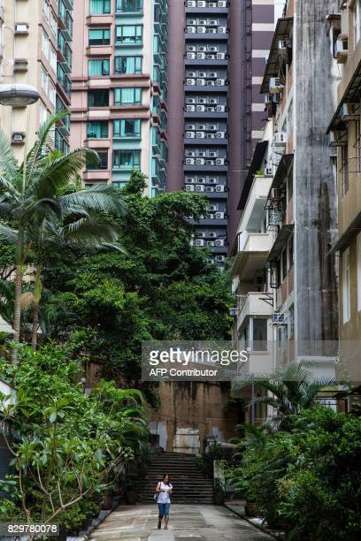 A migrant domestic worker walks down a path as highrise residential buildings installed with air conditioning units are seen in the background in...