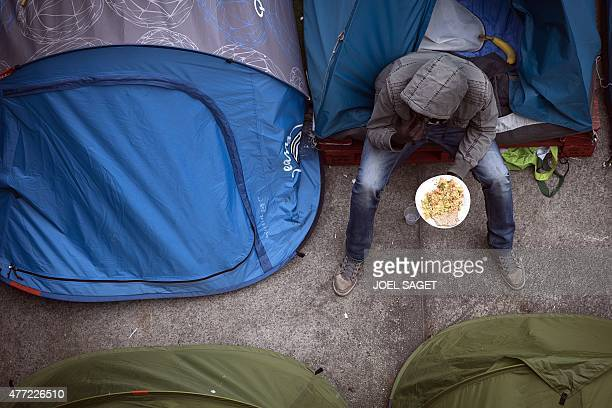 A migrant eats a meal outside his tent after it was distributed by volunteers in a camp located next to the Austerlitz station in Paris on June 14...