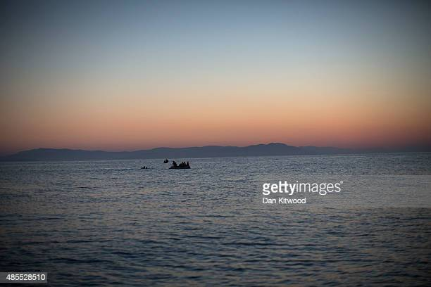 Migrant families from Syria in the distance prepare to arrive in an inflatable dinghy on the beach at sunrise on the island of Kos after crossing a...
