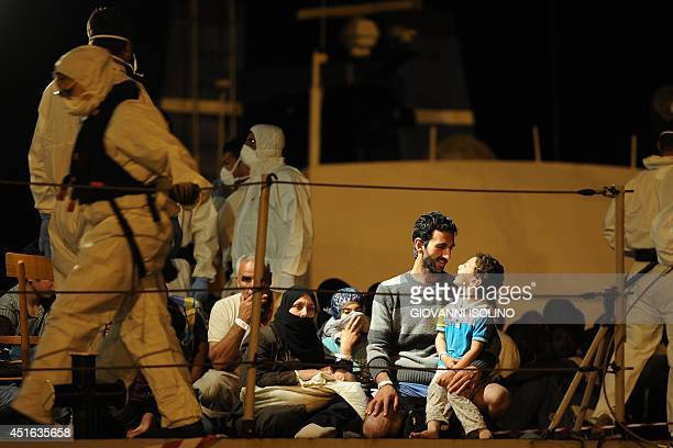 Migrant families wait to disembark from the Italian military ship 'Grecale' as they arrived in the port of Pozzallo Sicily on July 2 2014 two days...