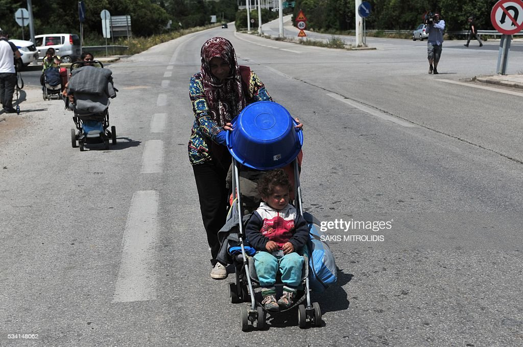 Migrant families with their children leave on foot the Idomeni camp along the Greek-Macedonian border because they do not want to be bussed to another camp on May 25, 2016. In an operation which began shortly after sunrise on May 24, hundreds of Greek police began evacuating the sprawling camp which is currently home to 8,400 refugees and migrants, among them many families with children, an AFP correspondent said. At its height, there were more than 12,000 people crammed into the site, many of them fleeing war, persecution and poverty in the Middle East and Asia, with the camp exploding in size since Balkan states began closing their borders in mid February in a bid to stem the human tide seeking passage to northern Europe. / AFP / SAKIS