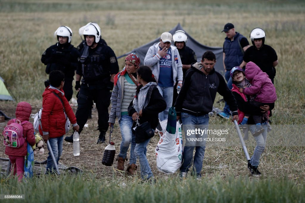 A migrant family carries their belongings during an evacuation operation by police forces of a makeshift migrant camp at the border at the Greek-Macedonian border near the village of Idomeni, on May 24, 2016. In an operation which began shortly after sunrise on May 24, hundreds of Greek police began evacuating the sprawling camp which is currently home to 8,400 refugees and migrants, among them many families with children, an AFP correspondent said. At its height, there were more than 12,000 people crammed into the site, many of them fleeing war, persecution and poverty in the Middle East and Asia, with the camp exploding in size since Balkan states began closing their borders in mid February in a bid to stem the human tide seeking passage to northern Europe. / AFP / POOL / YANNIS