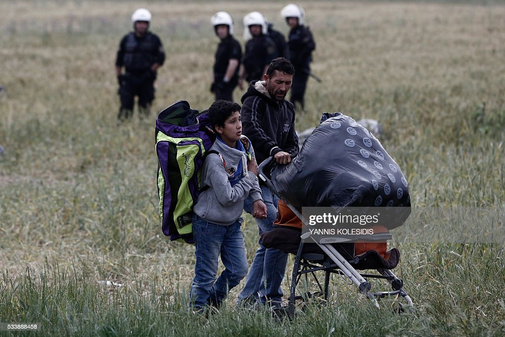 A migrant family carries their belongings during an evacuation operation by police forces of a makeshift migrant camp at the border at the Greek-Macedonian border near the village of Idomeni, on May 24, 2016. In an operation which began shortly after sunrise on May 24, hundreds of Greek police began evacuating the sprawling camp which is currently home to 8,400 refugees and migrants, among them many families with children, an AFP correspondent said. At its height, there were more than 12,000 people crammed into the site, many of them fleeing war, persecution and poverty in the Middle East and Asia, with the camp exploding in size since Balkan states began closing their borders in mid February in a bid to stem the human tide seeking passage to northern Europe. / AFP / POOL / Yannis KOLESIDIS