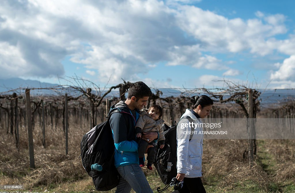 A migrant family crosses the Greek-Macedonian border near the town of Gevgelija, on February 14, 2016. Dutch Foreign minister Bert Koenders on February 14, 2016 spent an hour in a Vinojug recipient center near Gevgelija talking with migrants, children, UNICEF and Red Cross representatives, police and others members who are taking care of migrants heading to the EU from devastated homes in Syria, Afghanistan and Iraq. / AFP / Robert ATANASOVSKI