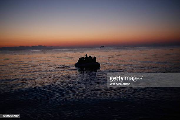 A migrant family from Syria arrives in a small boat as the sun rises on the island of Kos after crossing a three mile stretch of the Aegean Sea from...
