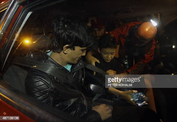 A migrant family is helped by a driver of an Austrian car rescue convoy to transport migrant people in Budapest on September 6 2015 as more than 140...