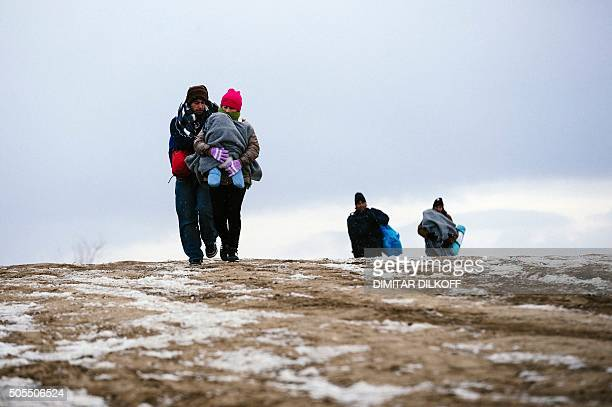 TOPSHOT A migrant family walks through a snowy field after crossing the Macedonian border into Serbia near the village of Miratovac on January 18...