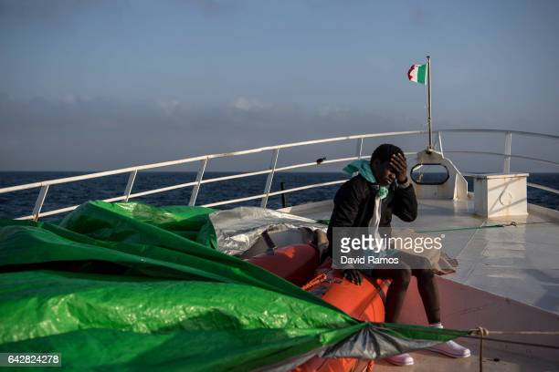 A migrant feels sick on deck of the Spanish NGO Proactiva Open Arms rescue vessel Golfo Azzurro sailing towards the Italian port of Pozzallo after...