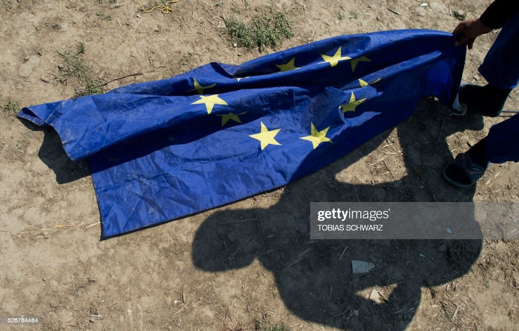 A migrant from Afghanistan grabs for an EU flag next to his tent at a makeshift camp for migrants and refugees near the village of Idomeni not far from the Greek-Macedonian border on May 1, 2016. Some 54,000 people, many of them fleeing the war in Syria, have been stranded on Greek territory since the closure of the migrant route through the Balkans in February. / AFP / TOBIAS