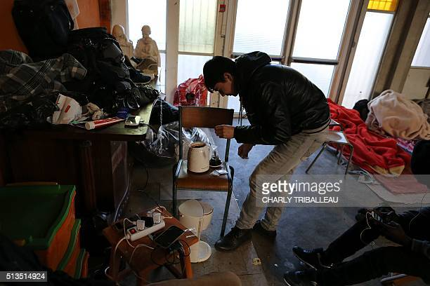 A migrant from Afghanistan prepares tea in the premises of a former church where sixty migrants hoping to take a ferry from Cherbourg to Portsmouth...