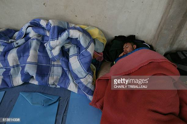 A migrant from Afghanistan sleeps in the premises of a former church where sixty migrants hoping to take a ferry from Cherbourg to Portsmouth in...
