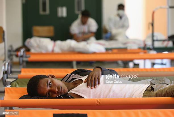 A migrant from Eritrea rests on a cot while waiting during his registration process at a center for migrants at a facility of the German Federal...