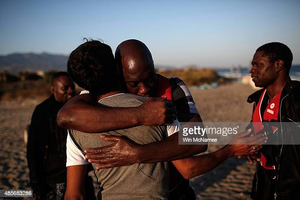 A migrant from Gambia embraces a friend after safely completing a journey across a three mile stretch of the Aegean Sea in a small boat from Turkey...