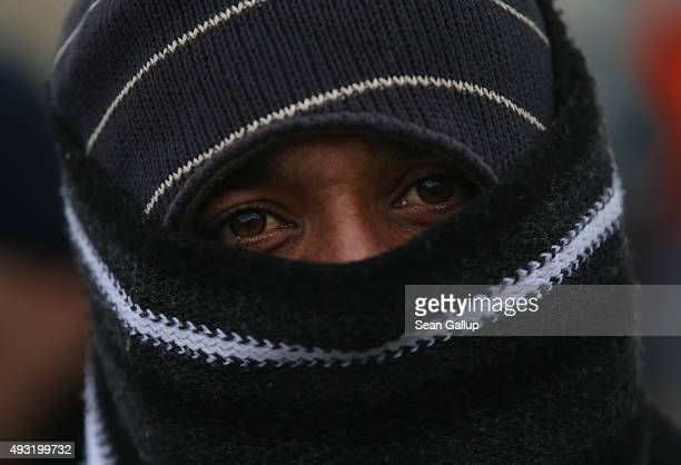 A migrant from Pakistan who had arrived on a bus chartered by Austrian authorities wraps his face in a scarf against the cold before continuing...