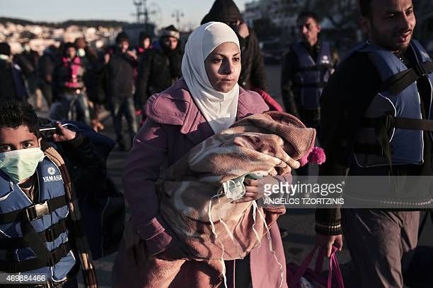 A migrant from Syria holds her child upon arrival in Greece at the port of Lesbos island on April 16 2015 The decision was made at an emergency...