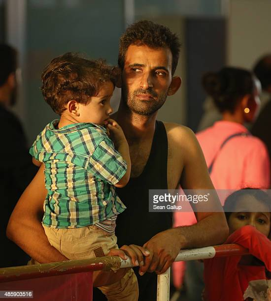 A migrant from Syria holds one of his children in a holding area after arriving at Munich Hauptbahnhof main railway station and being detained by...