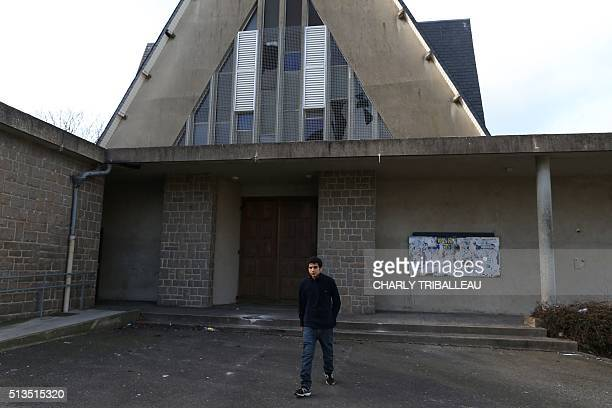 A migrant from Syria is pictured in front of a former church where sixty migrants hoping to take a ferry from Cherbourg to Portsmouth in Britain live...