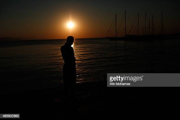 A migrant from Syria prays as the sun rises alongside the town port on August 30 2015 in Kos Greece From Kos many migrants journey north to Athens...