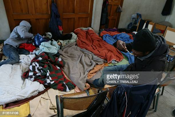 A migrant from Uganda eats in a former church where sixty migrants hoping to take a ferry from Cherbourg to Portsmouth in Britain live in...