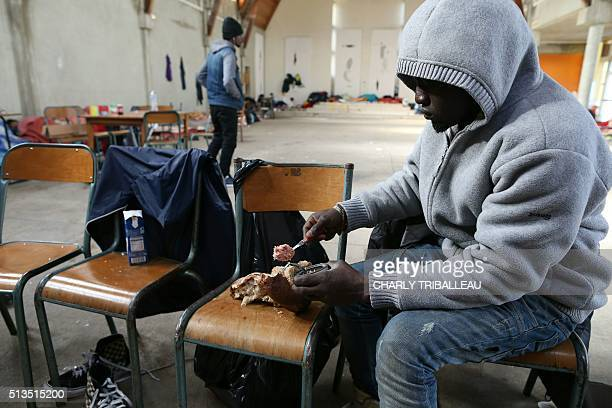 A migrant from Uganda eats in the premises of a former church where sixty migrants hoping to take a ferry from Cherbourg to Portsmouth in Britain...
