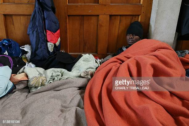 A migrant from Uganda rests in the premises of a former church where sixty migrants hoping to take a ferry from Cherbourg to Portsmouth in Britain...