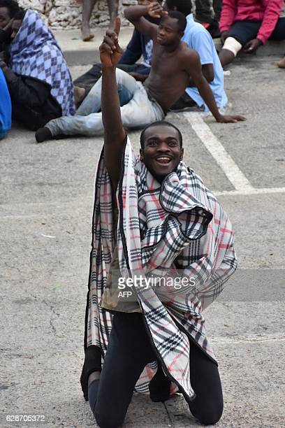 A migrant gestures from the ground in El Tarajal Ceuta close to the boarder with Morocco on December 9 2016 after being rounded up by police to be...