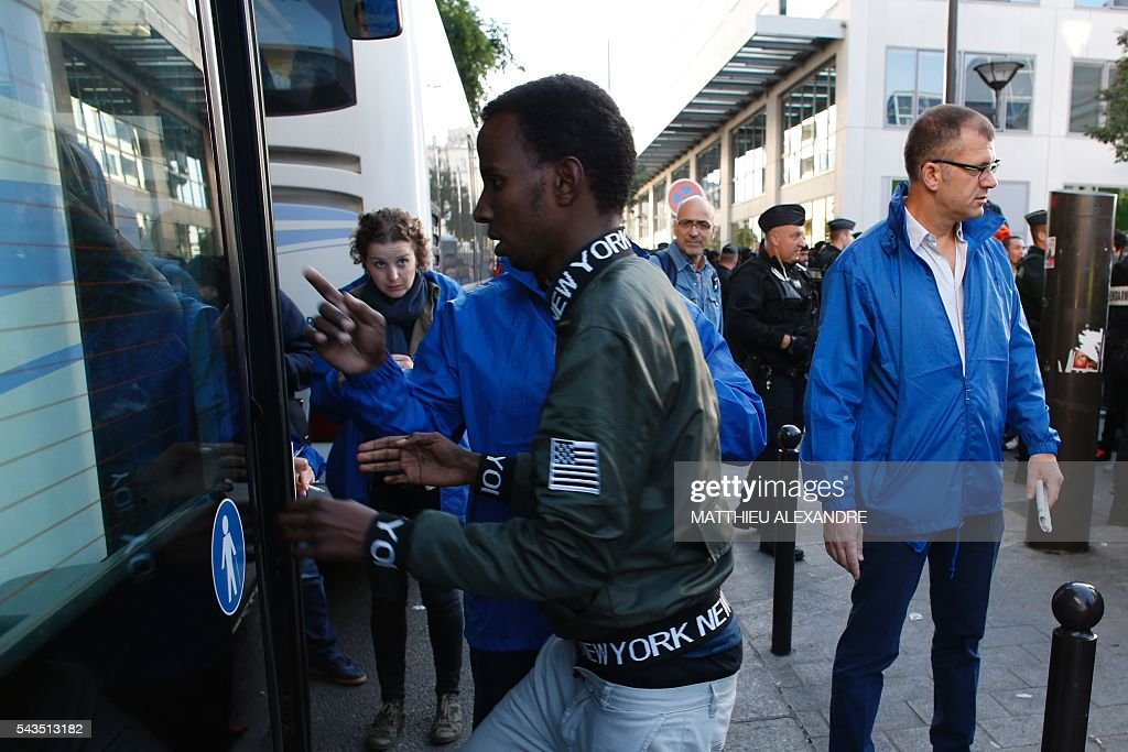 A migrant gets on a bus as the French Gendarmerie proceeds to the evacuation of migrants at the Pajol hall on June 29, 2016 in Paris. The police started early on June 29, 2016, the evacuation of several hundreds of migrants, from a camp at the former SNCF Hall 'Pajol'. / AFP / MATTHIEU
