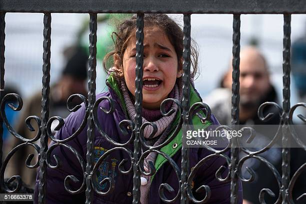 A migrant girl cries as she waits at a Turkish coast guard station at the Dikili district in Izmir on March 20 after being caught with other migrants...