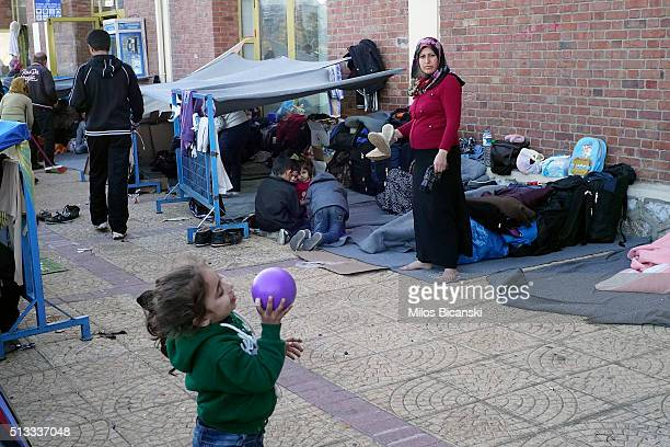 A migrant girl from Syria plays with a ball in front of improvised shelter outside a passenger terminal at the port of Piraeus on March 2 2016 in...